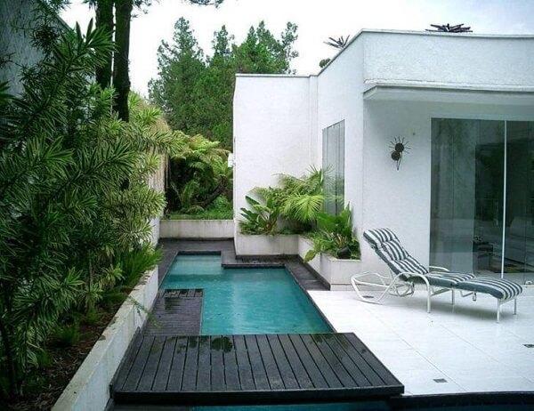 Casa moderna com revestimento de concreto. e piscina pequena.