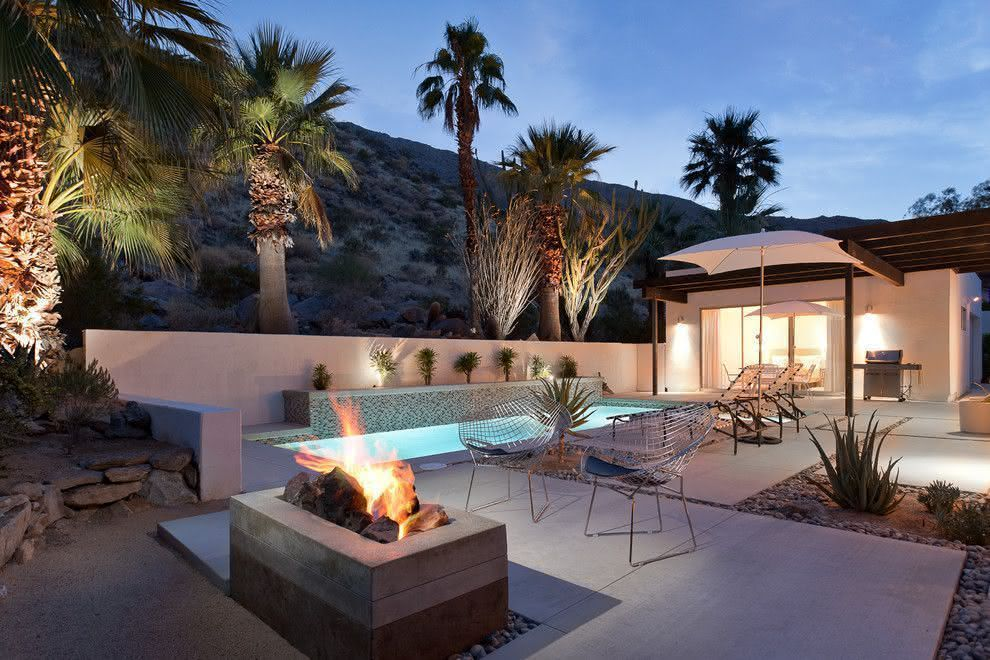 Área externa moderna com piscina pequena iluminada.