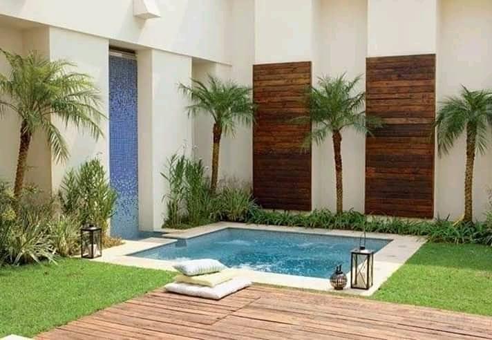 Área externa com parede revestida de madeira, piscina pequena e fonte.