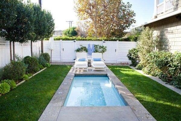 Jardim com piscina pequena retangular.