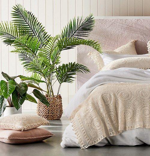 Vaso de planta ao lado da cama de casal.
