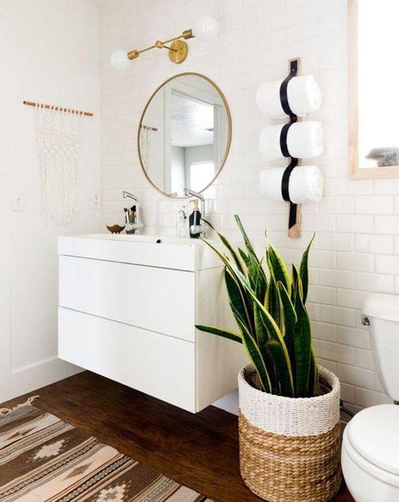Banheiro com vaso de folhas entre a pia e o vaso.