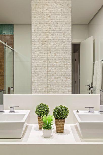 Pia de banheiro com três vasos de plantas para dentro de casa.