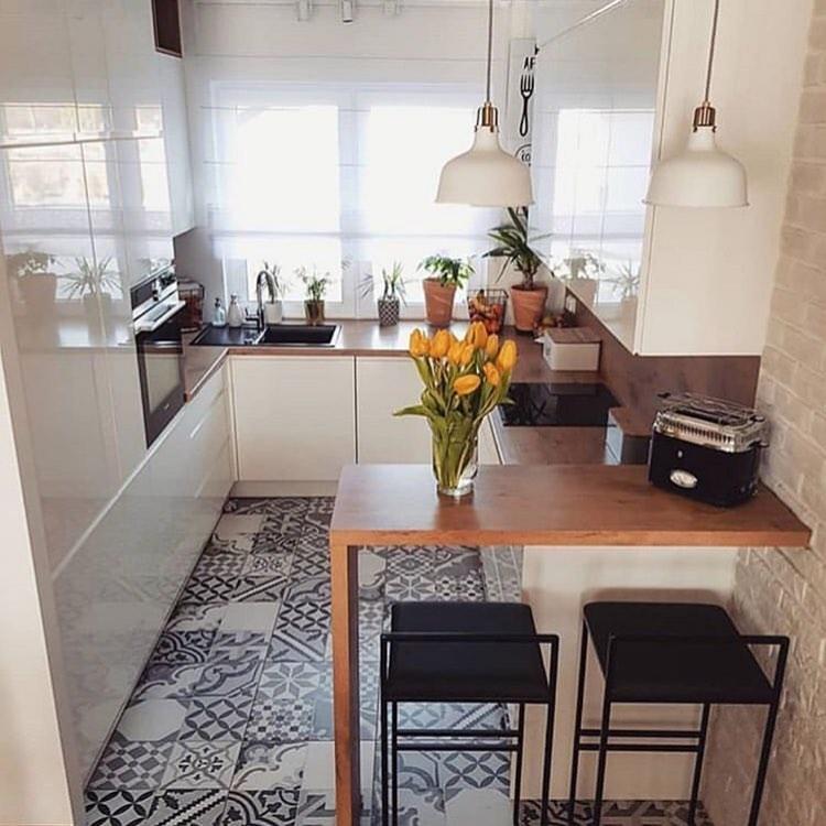Cozinha americana pequena com piso de ladrilho hidráulico.