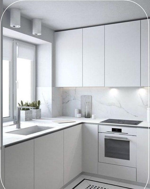 Decoração com mármore e armários brancos minimalistas.