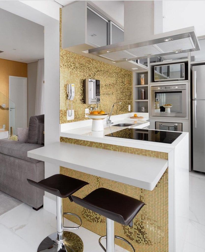 Cozinha americana com pastilhas de vidro metalizadas e douradas.