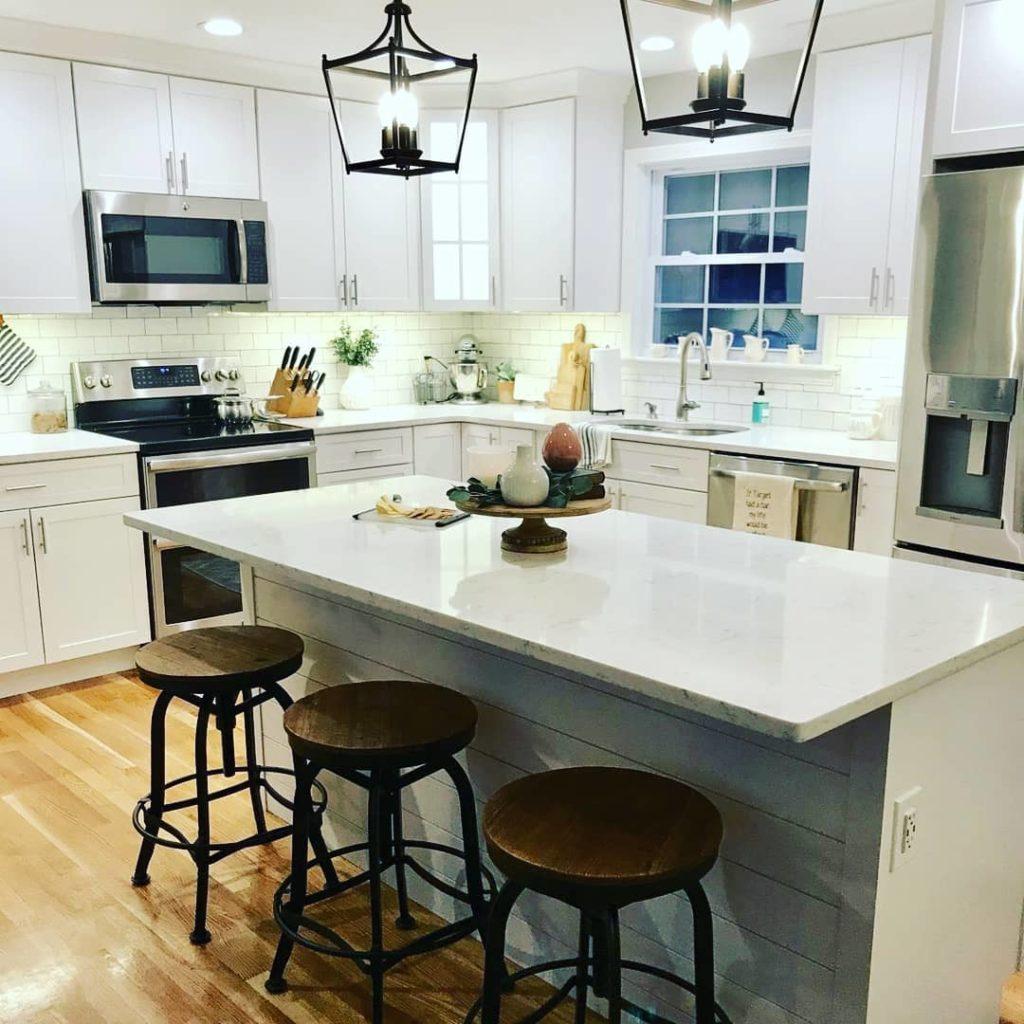 Cozinha com ilha branca com plaquetas de cerâmica.