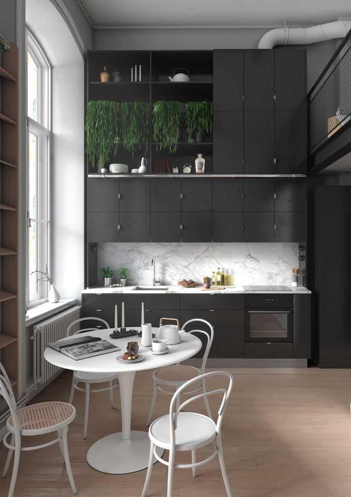 Cozinha preta com revestimento de mármore.