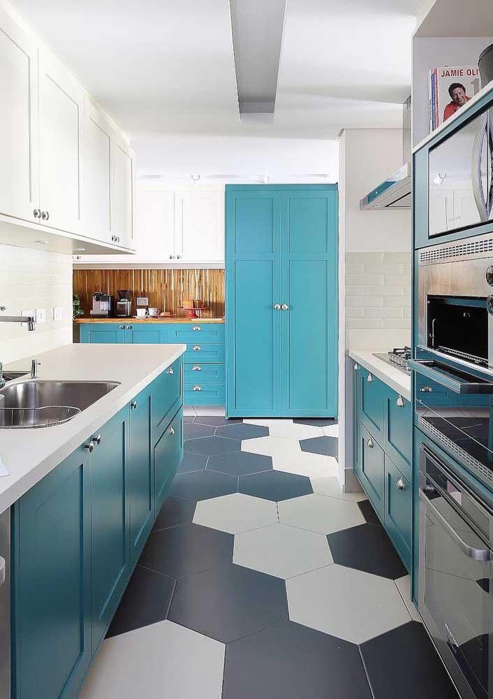Revestimentos para cozinha com armários azuis e piso geométrico.