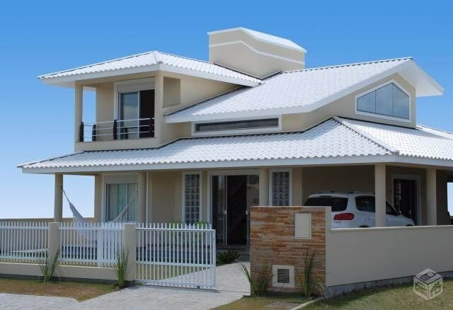 Tipos de telha: Casa com dois andares e telhado com telhas esmaltadas brancas.