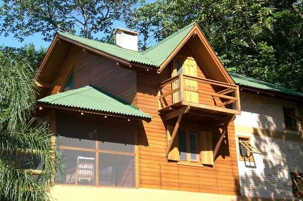 Tipos de telha: Casa de campo de madeira com telhas de fibra vegetal.