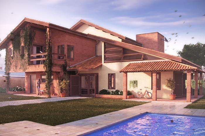 Casa de campo grande com parede de tijolinho e telhado com telhas de cerâmica.