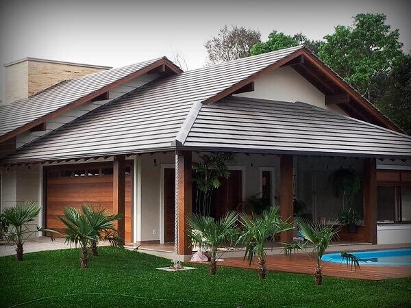 Tipos de telha: Casa ampla com piscina com telhado com telhas de concreto.