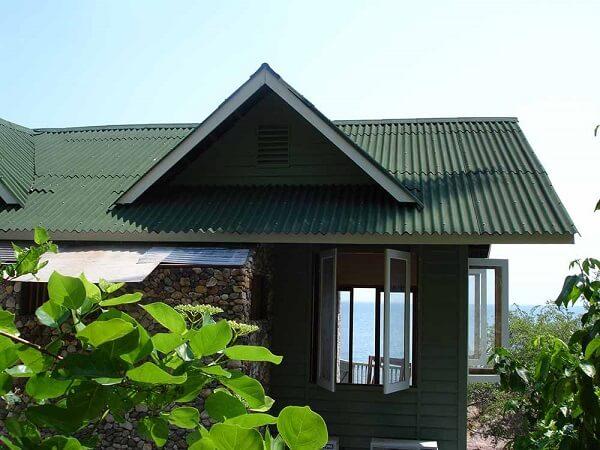 Tipos de telha: Casa de campo com parede de pedra e madeira com telhado verde de fibra vegetal.