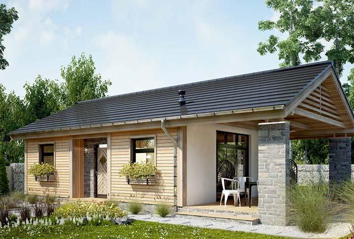 Casa de campo térrea pequena com telhado em duas águas com telhas granilhadas.