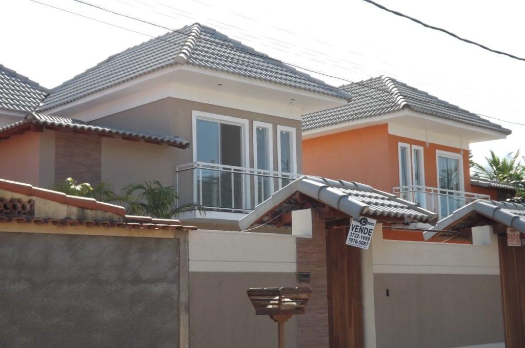 Casa com dois andares simples e telhado de concreto.