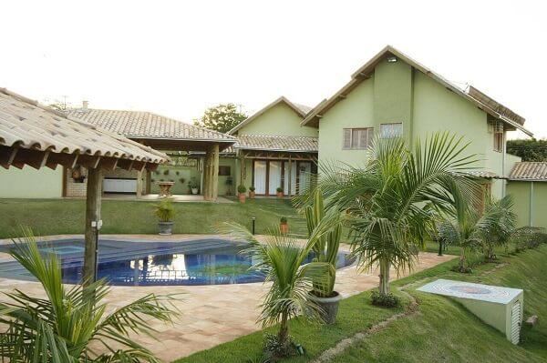 Casa com piscina e telhado de telhas claras.