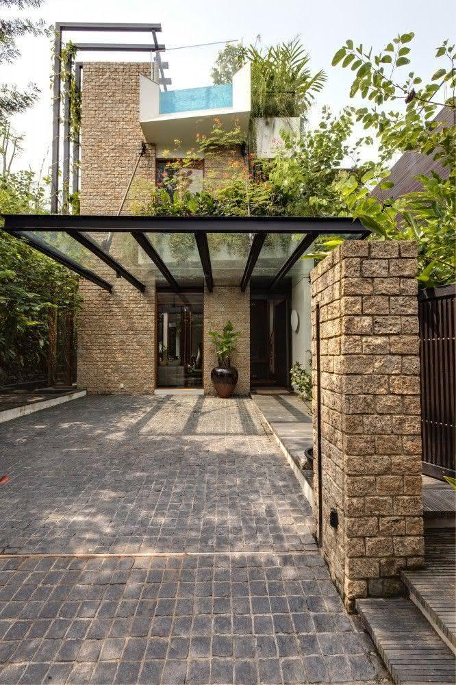 Cobertura para garagem de vidro com estrutura metálica.