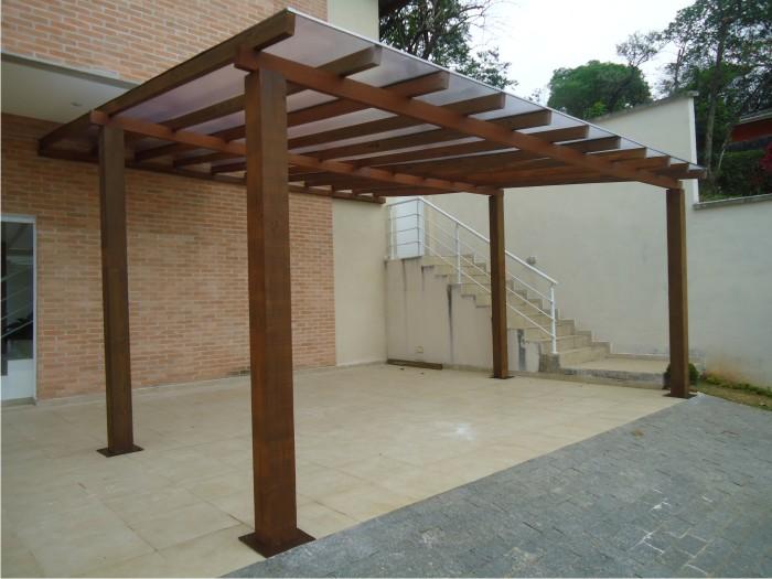 Cobertura para garagem com estrutura de madeira e policarbonato.