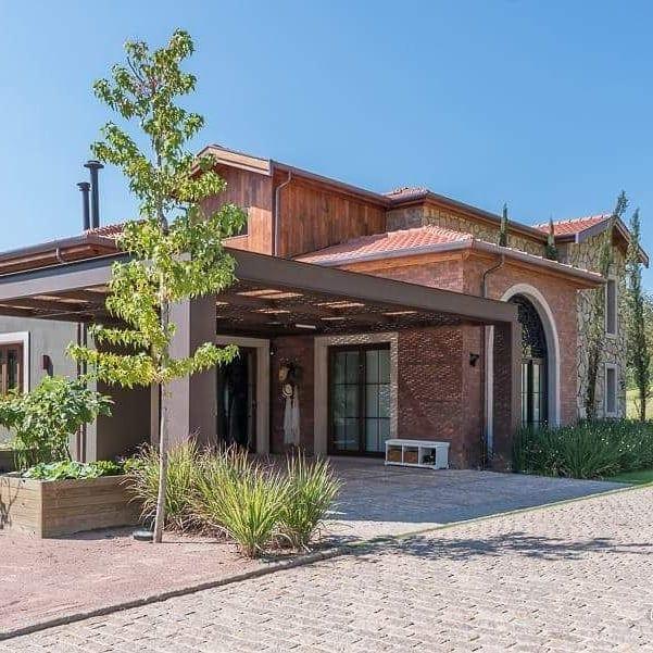 Casa rústica com cobertura para garagem de madeira.