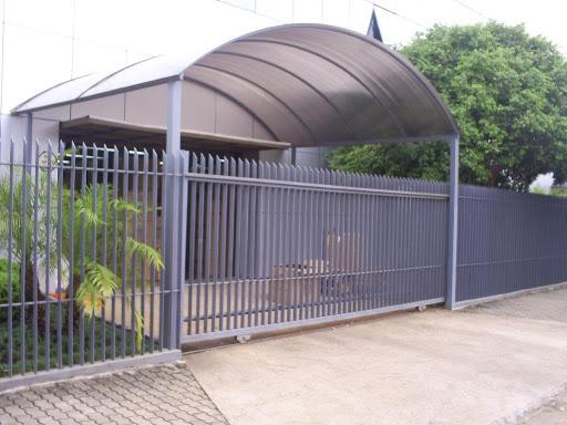 Estrutura metálica com telhado de policarbonato na entrada do prédio.