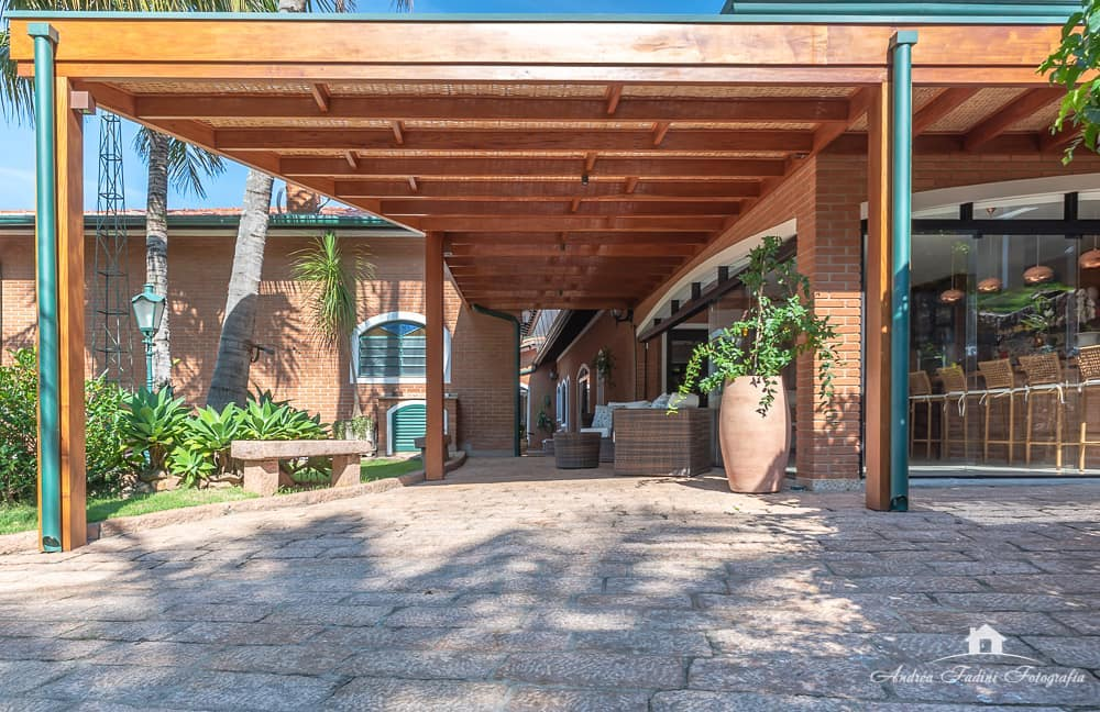 Casa rústica com estrutura de madeira para proteger carros.