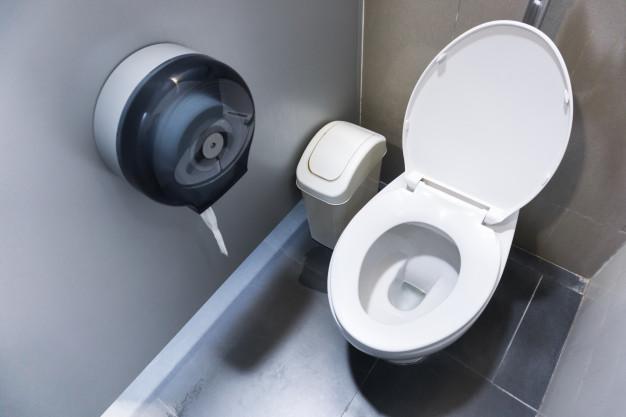 Banheiro com vaso, lixeira e suporte de papel higiênico.