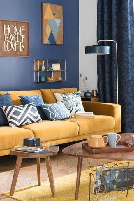 Sala com sofá amarela e parede azul.