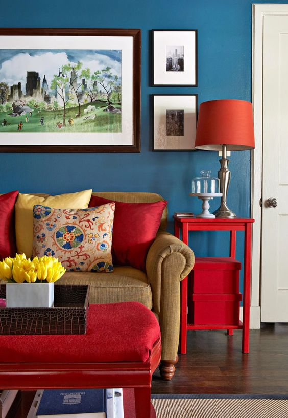 Sala com móveis vermelhos e parede azul.