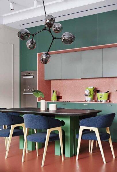 Cozinha aberta e moderna com armários verdes.