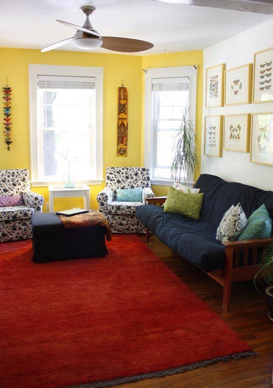 Sala simples com parede amarela.