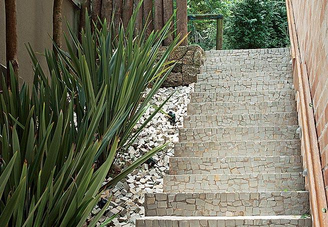 Jardim com pedras portuguesas e escada.