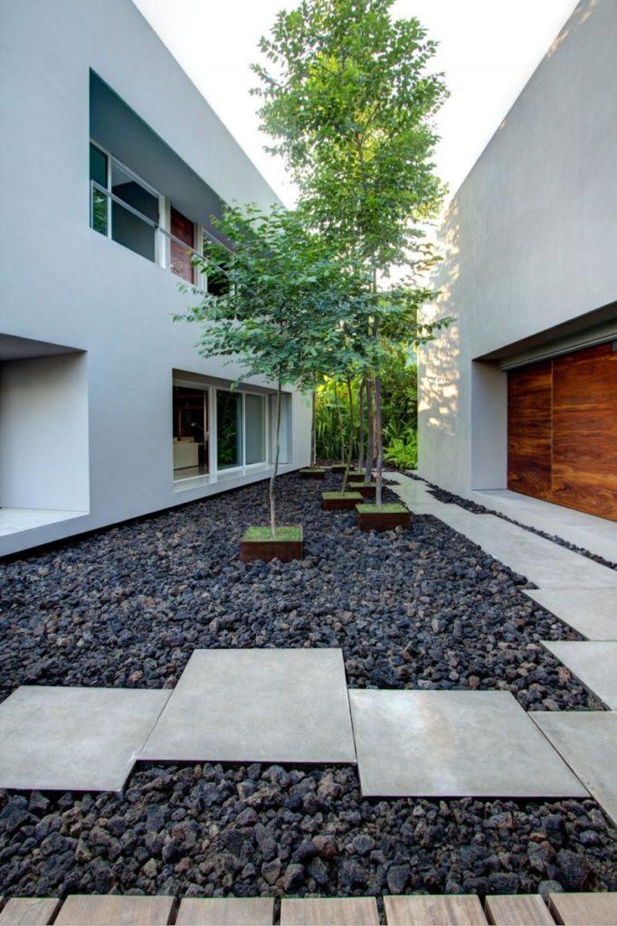 Área externa com decoração moderna e vasos de plantas.