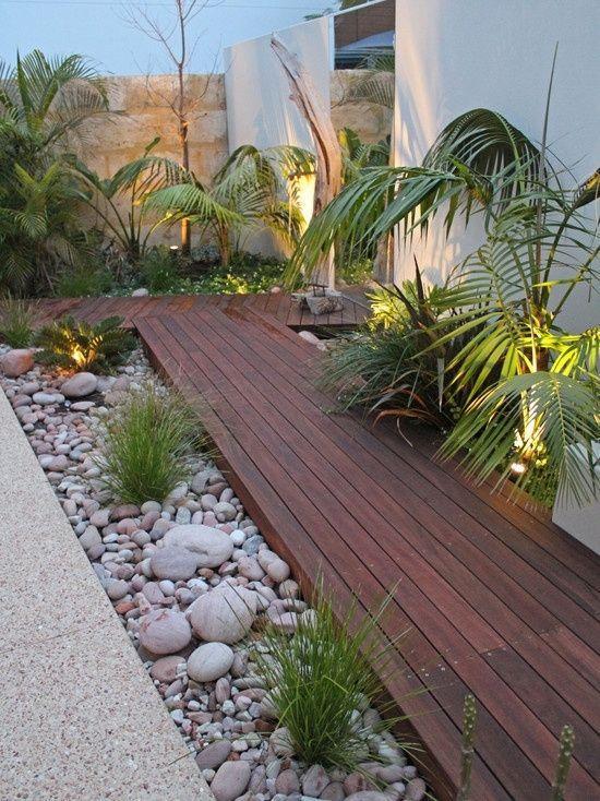 Jardim lateral com pedras de rio e passarela de madeira.