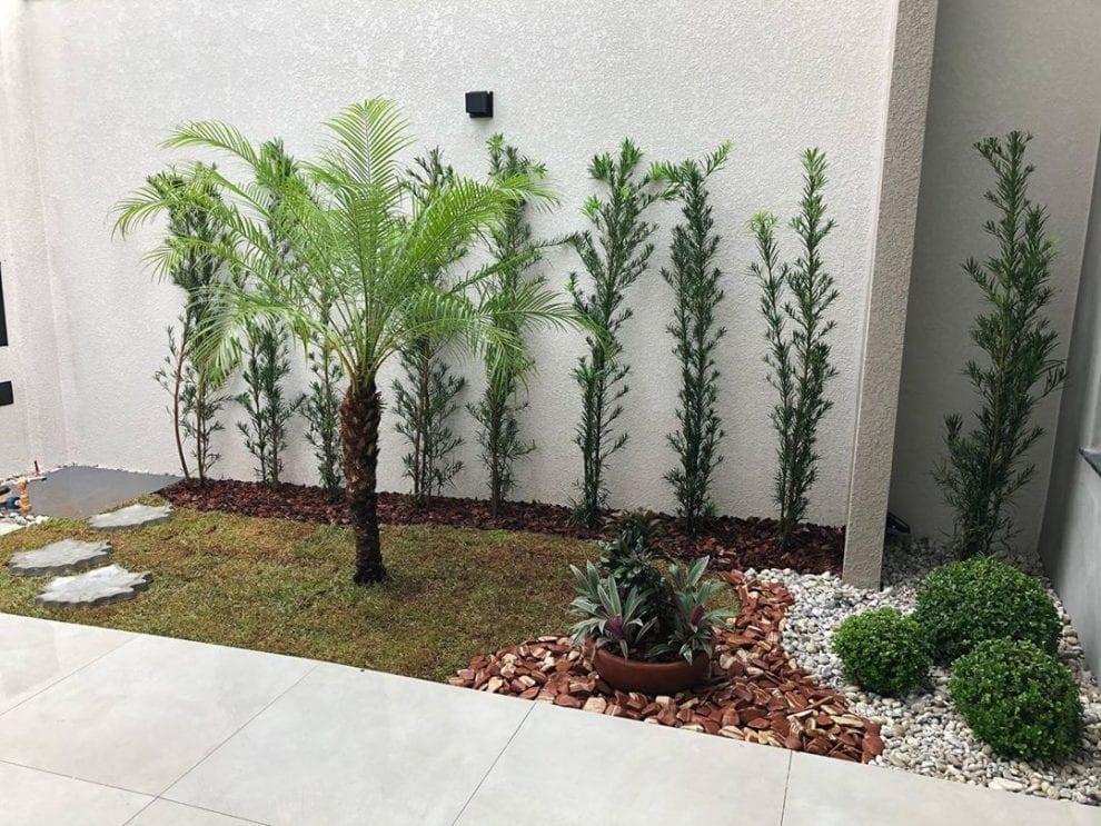 Jardim com pedras de rio, grama e palmeiras.