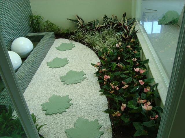 Jardim de inverno com passarela, fonte e várias espécies de plantas.