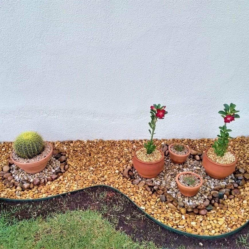 Jardim com pedras e vasos de barro.