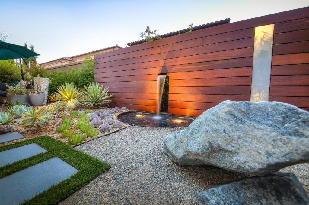 Área externa com fonte e parede de madeira.