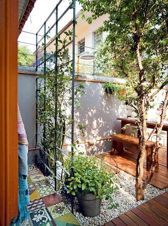 Jardim pequeno com árvore e grade.