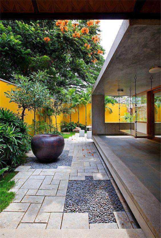 Área externa decorada com plantas e piso de brita.