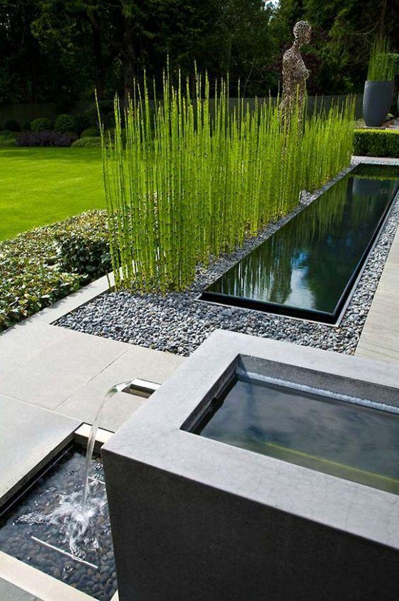 Jardim moderno com fonte e espelho d'água.