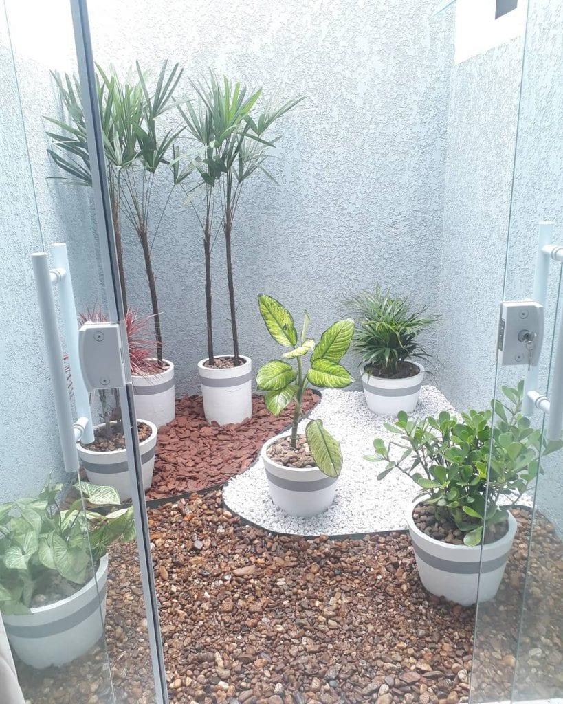 Jardim de inverno com pedras mistas e vasos de plantas.