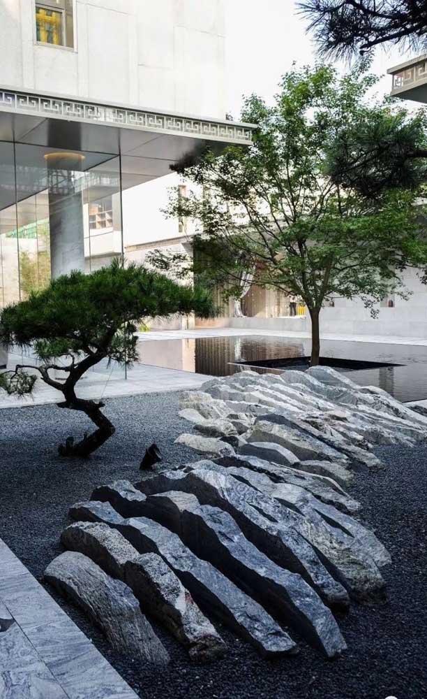 Área externa com decoração moderna e rochas gigantes.