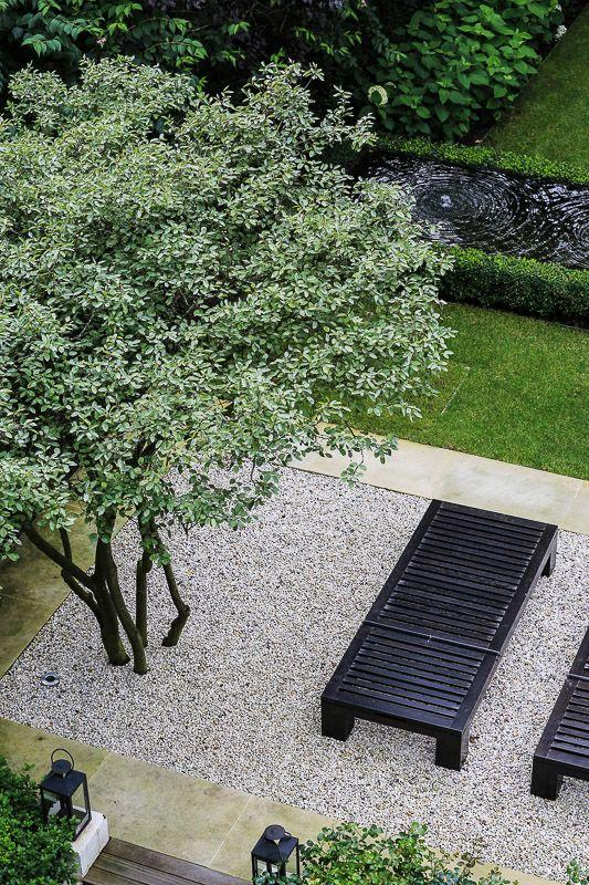 Jardim com pedras  de brita branca no piso.