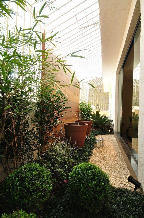 Jardim lateral com fontes e bambus.
