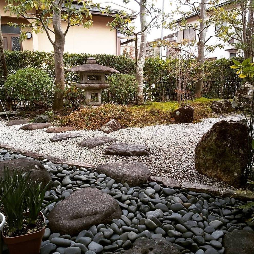 área externa com plantas, passarela rústica e escultura oriental.