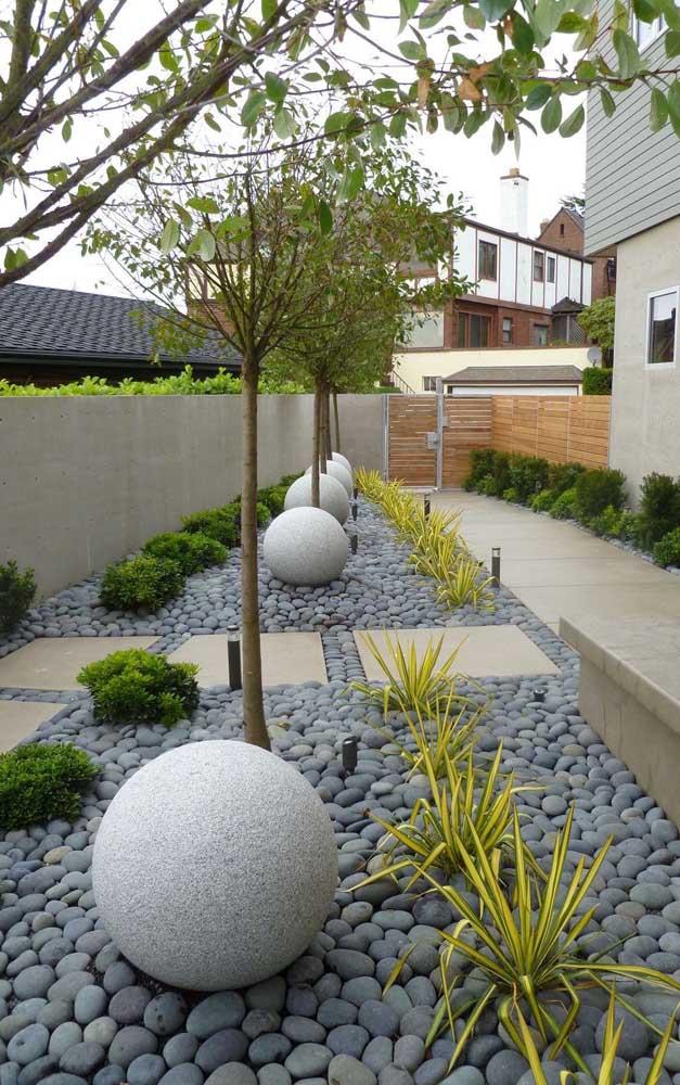 Área externa com rochas de rio e esculturas de concreto.