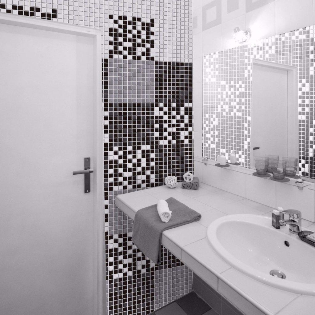 Papel de parede para banheiro com estampa pastilha preta e branca.