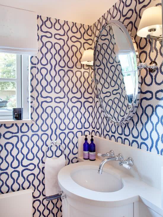 Banheiro com papel de parede om estampa moderna e azul.