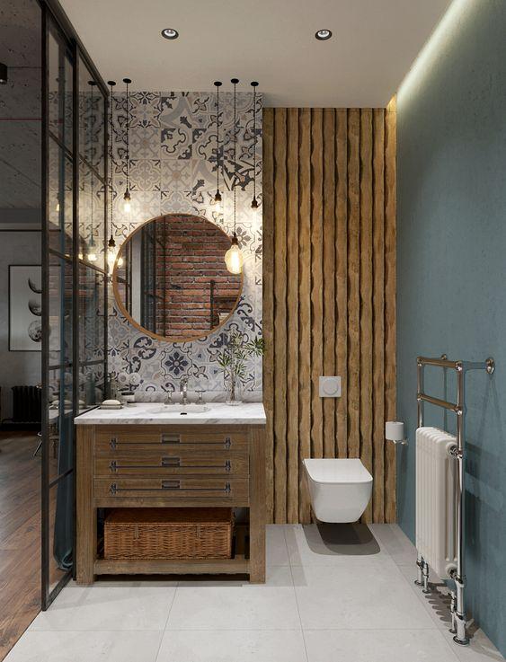 Decoração moderna com armário de madeira e espelho redondo.